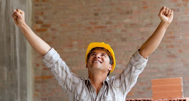 hard hat construction worker celebrates arm in air